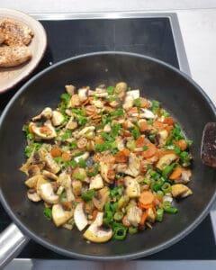 In einer Pfanne angedünstetes Gemüse auf dem Herd.