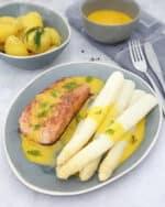 Spargel mit Lachs und Sauce Hollandaise auf einem blauen Teller. Im Hintergrund Deko.