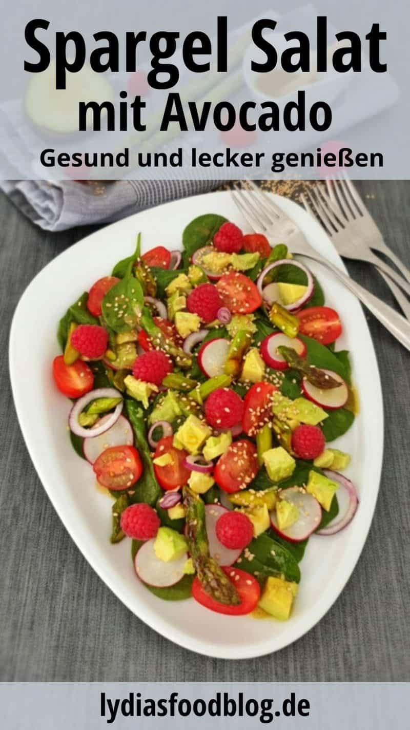 Auf einem weißen ovalen Teller angerichtet ein sommerlicher Salat mit Spargel, Avocado und Spinat.