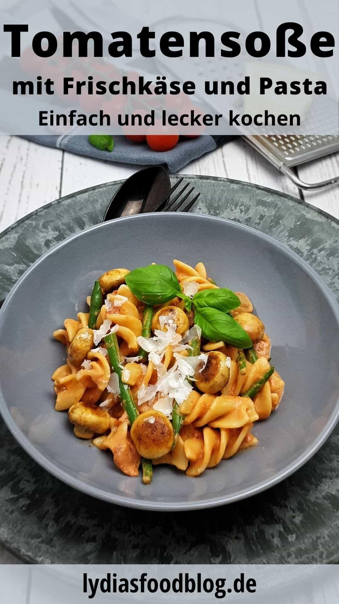 Pasta mit Pasta mit Tomaten-Frischkäse-Soße in einer grauen Schale angerichtet. Mit Parmesan bestreut und mit Basilikum serviert.
