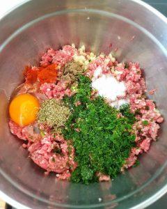 In einer silbernen Schale Hackfleisch für die Cevapcici mit dem Ei, der Petersilie und Gewürzen.