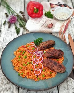 Cevapcici mit Djuvec Reis, ein Balkangericht, dekorativ angerichtet und mit roten Zwiebeln und Petersilie garniert in Szene gesetzt