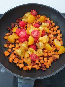 In einer Pfanne angebratene Süßkartoffel Würfel mit geschmorten gelben und roten Tomaten.