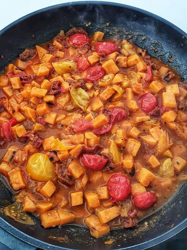 In einer Pfanne Tomatensugo mit Süßkartoffeln und bunten Tomaten.