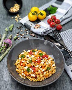 Ein sommerliches Pastagericht mit Fusilli Nudeln, Tomaten und Süßkartoffeln garniert mit Feta, Pinienkernen und Petersolie dekorativ angerichtet