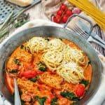 In einer gußeisernen Pfanne siehst man das Hähnchenfilet in cremiger Frischkäse-Parmesan-Soße mit Spaghetti Nestern angerichtet. In der Soße zu sehen frische kleine Tomaten und grüner Spinat. Die Spaghetti Nester sind mit Parmesan bestreut.