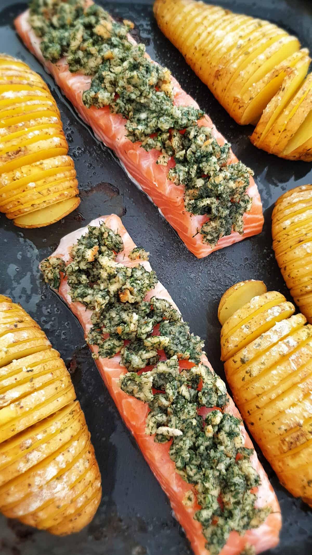 Lachsfilet mit Brotkruste und Fächerkartoffeln auf einem Backblech.