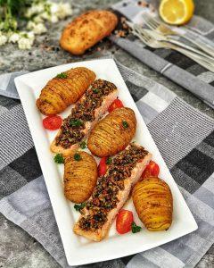 Lachs mit Brotkruste und Fächerkartoffeln aus dem Backofen dekorativ angerichtet auf einer weißen Servierplatte mit Petersilie bestreut.