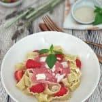 Bandnudeln mit Erdbeersoße und weißen Schokoraspeln dekorativ mit einem Basilikumblatt dekoriert.