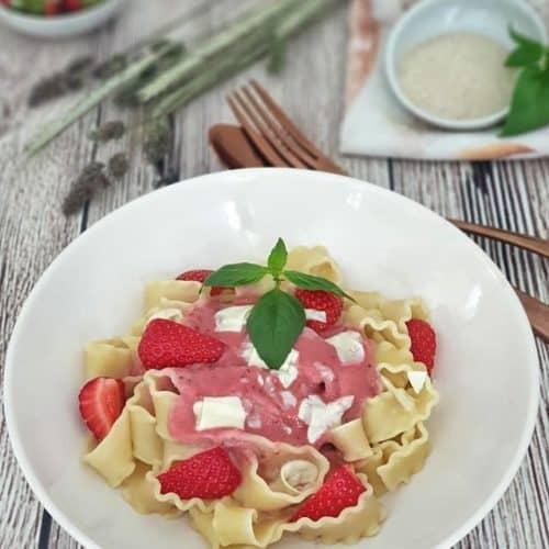 Bandnudeln mit Erdbeersoße und weißen Schokoraspeln in einem hellen Teller.