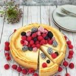 Ein Käsekuchen oder auch Cheescake mit frischen Himbeeren, ein paar Heidelbeeren und Brombeeren dekoriert und dekorativ angerichtet
