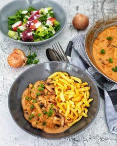 Spätzle mit Züricher Geschnetzeltes dekorativ in einer grauen Schale angerichtet, im Hintergrund ein frischer Salat