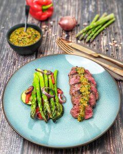 Rinderhüftsteak mit Chimicchuri angerichtet auf einem blauen Teller mit einem Spargel Gemüse