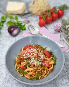 Pasta bella italia mit Hackfleischsoße, Rucola und frischen Tomaten dekarativ angerichtet mit Parmesan bestreut in einer grauen Schale