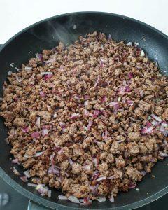 In einer Pfanne angebratene Zwiebel- und Knoblauch Würfel.