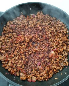 In einer Pfanne angebratenes Hackfleisch mit Zwiebeln, Tomatenmark und Rotwein.