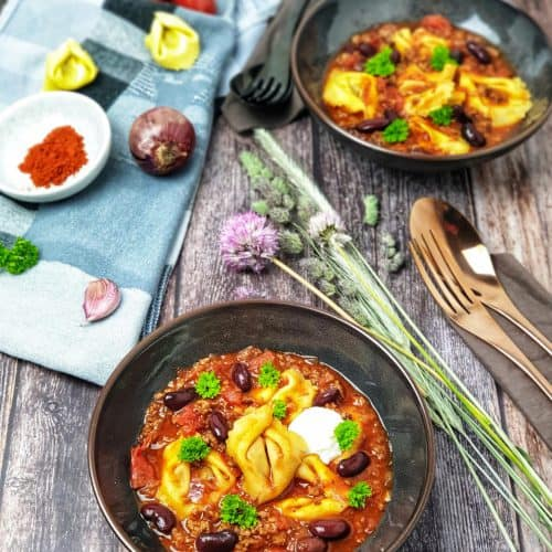 In einer braunen Schale serviert ein Tortellini-Suppe mit Hackfleisch und Kidneybohnen.