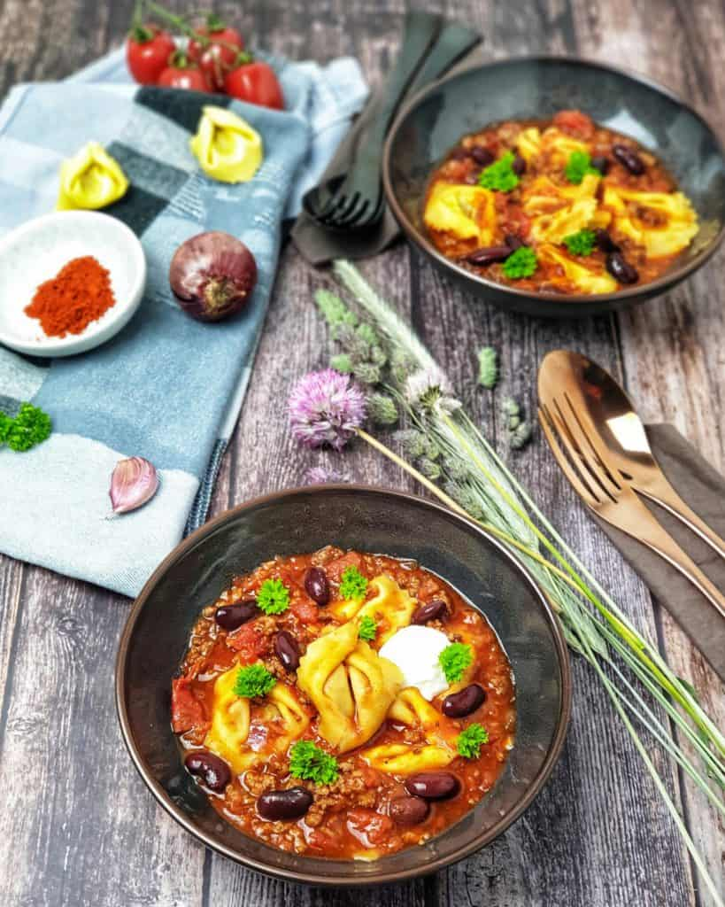 Eine Chilli con Tortellini Suppe mit Hackfleisch und Kidneybohnen, dekorativ angerichtet mit einem Klecks Creme fraiche in einer braunen Schale