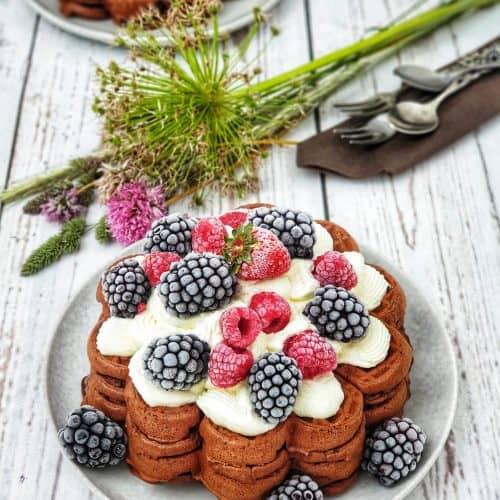 Schoko Waffeln mit Sahne und gefrorenen Beeren dekorativ auf einem Teller angerichtet und fotografiert.Im Hintergrund ein Teller mit gestapelten Waffeln und eine kleines Wildblumensträußchen.