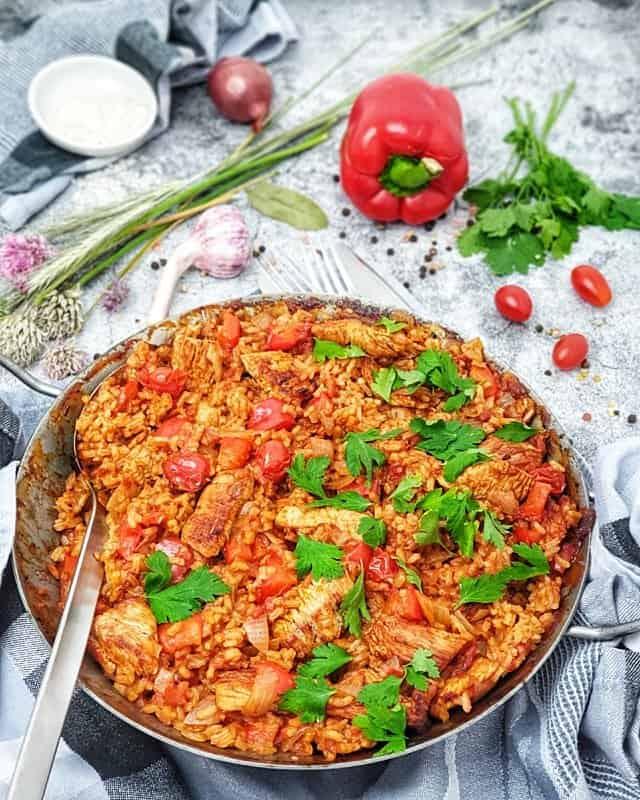 Eine Reispfanne mit Pute, Tomaten und Paprika aus dem Backofen. Mit Petersilie bestreut.