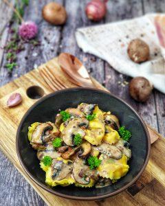 Vegetarische Tortellini mit Pilz-Rahm-Soße dekorativ angerichtet und mit Petersilie bestreut.