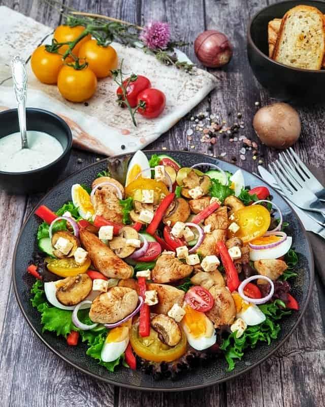 Auf einem dunklen Teller angerichtet ein bunter Salat mit Ei und Hähnchen. Im Hintergrund sieht man ein Schälchen mit Joghurt Dressing.