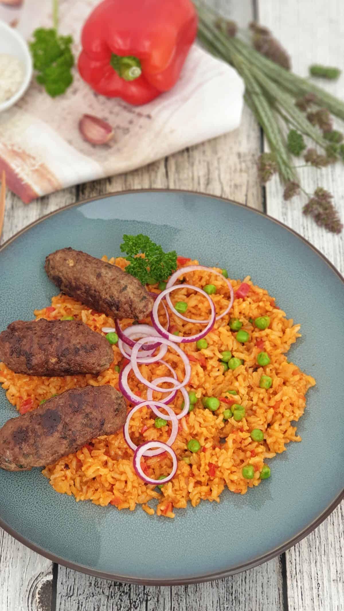 Auf einem blauen Teller Cevapcici mit Djuveč-Reis. Mit roten Zwiebelringen garniert. Im Hintergrund Deko.