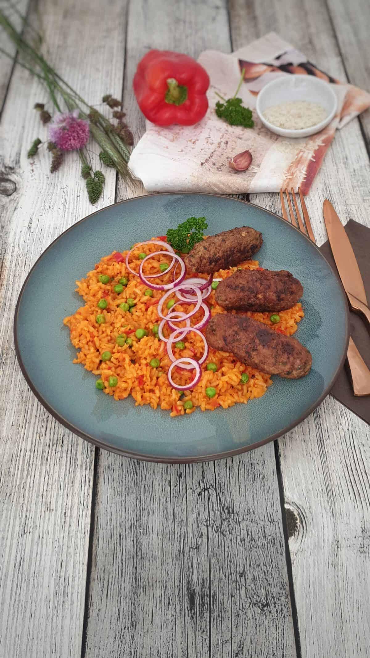 Auf einem blauen Teller Cevapcici mit Djuveč Reis. Mit roten Zwiebelringen garniert. Im Hintergrund Deko.
