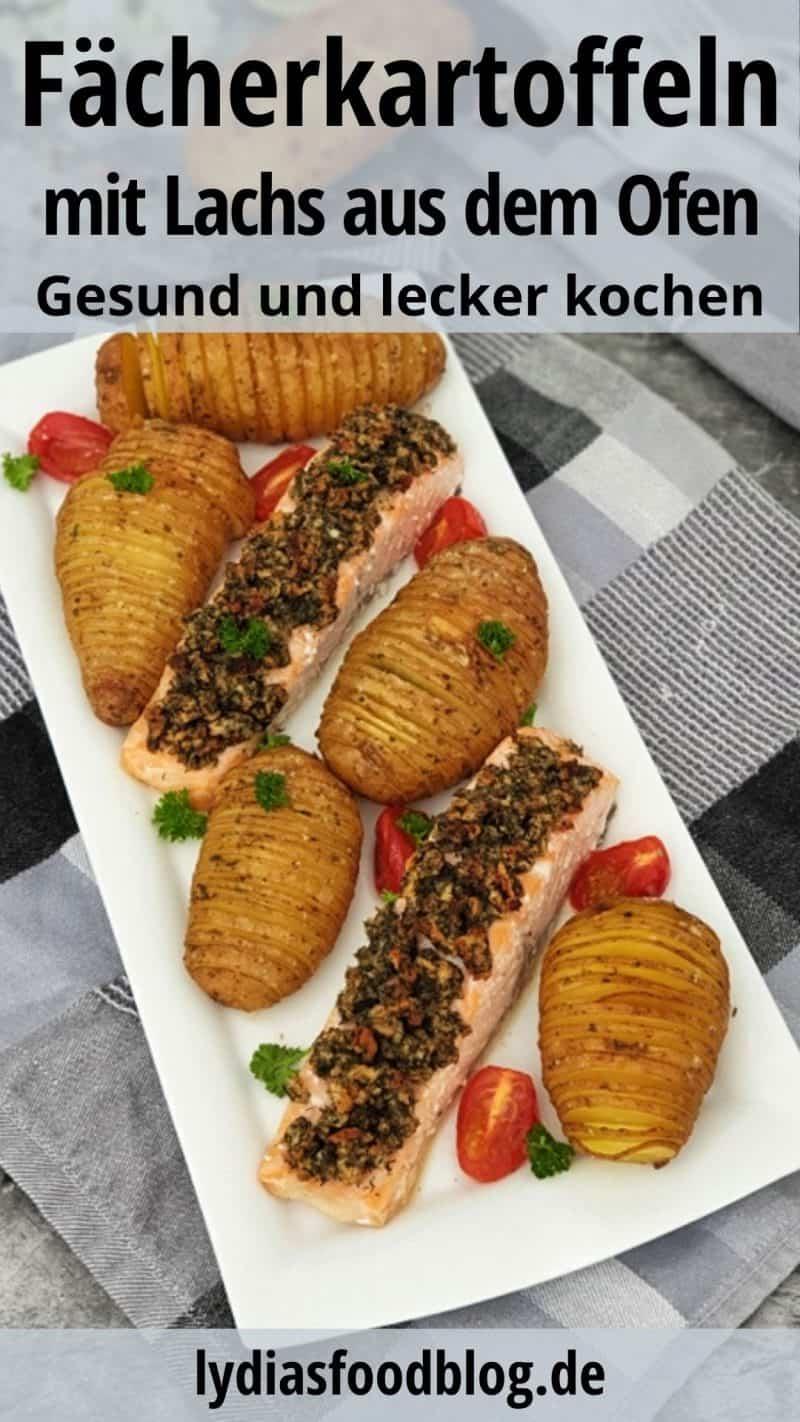 Auf einer weißen Platte angerichtet Fächerkartoffeln mit Lachs aus dem Ofen. Die Platte steht auf einem grauen Küchenhandtuch. Im Hintergrund liegt Besteck.