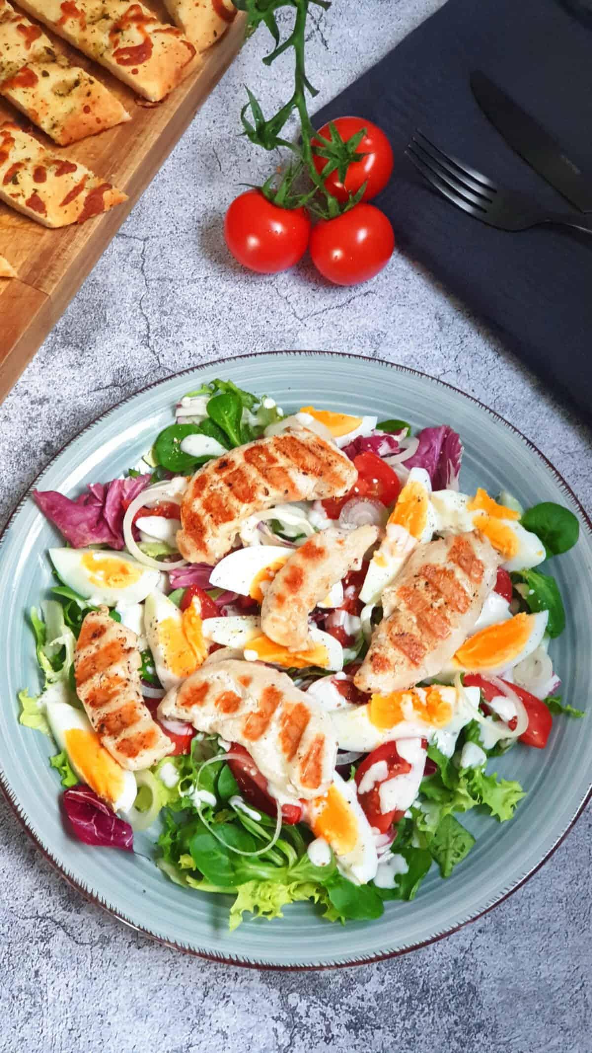 Auf einem grünen Teller sieht man einen frischen Salat mit gegrilltem Hähnchen und mit Joghurt Dressing.
