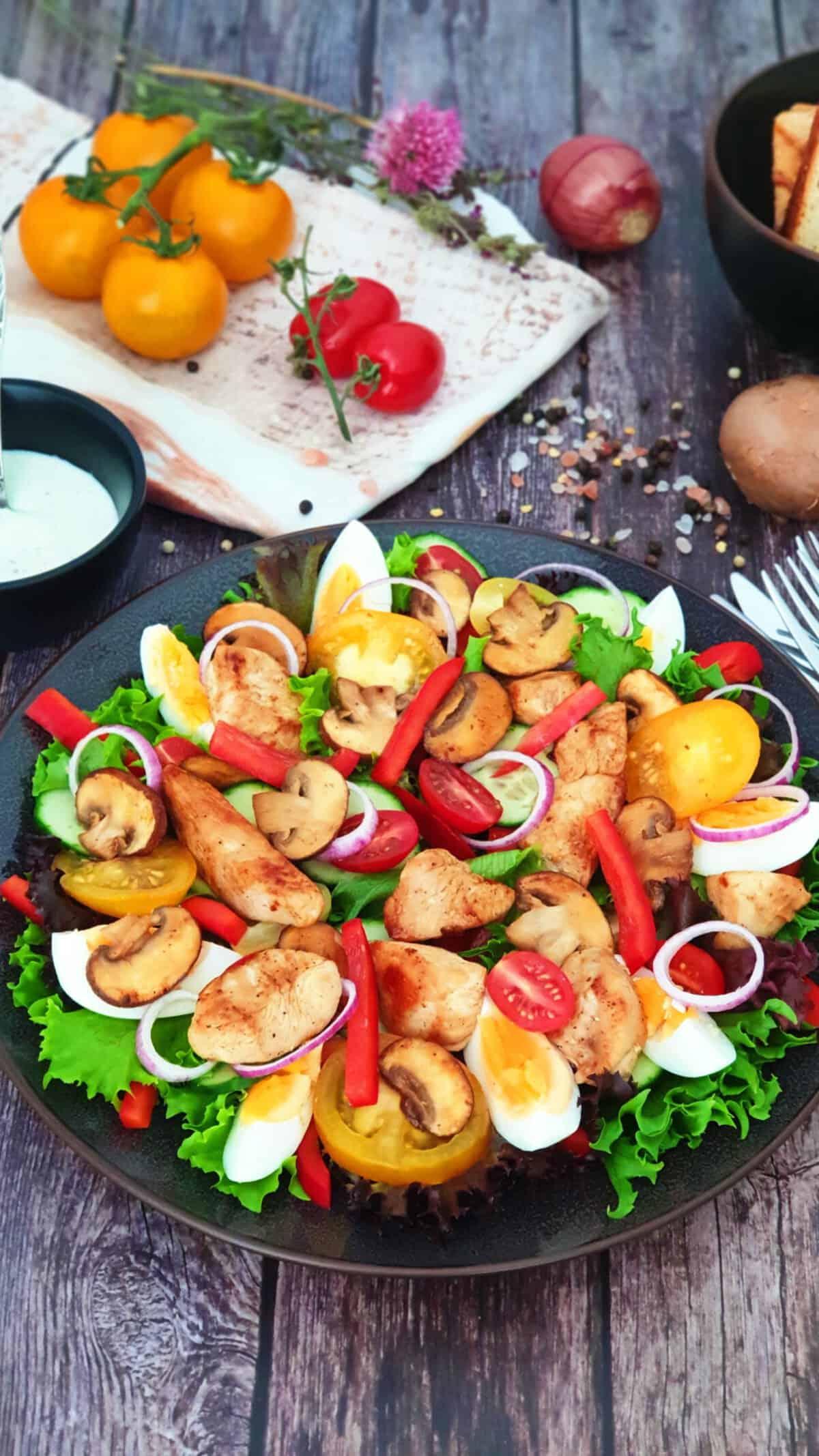 Auf einem grünen Teller sieht man einen frischen Salat mit Hähnchen und mit Joghurt Dressing.