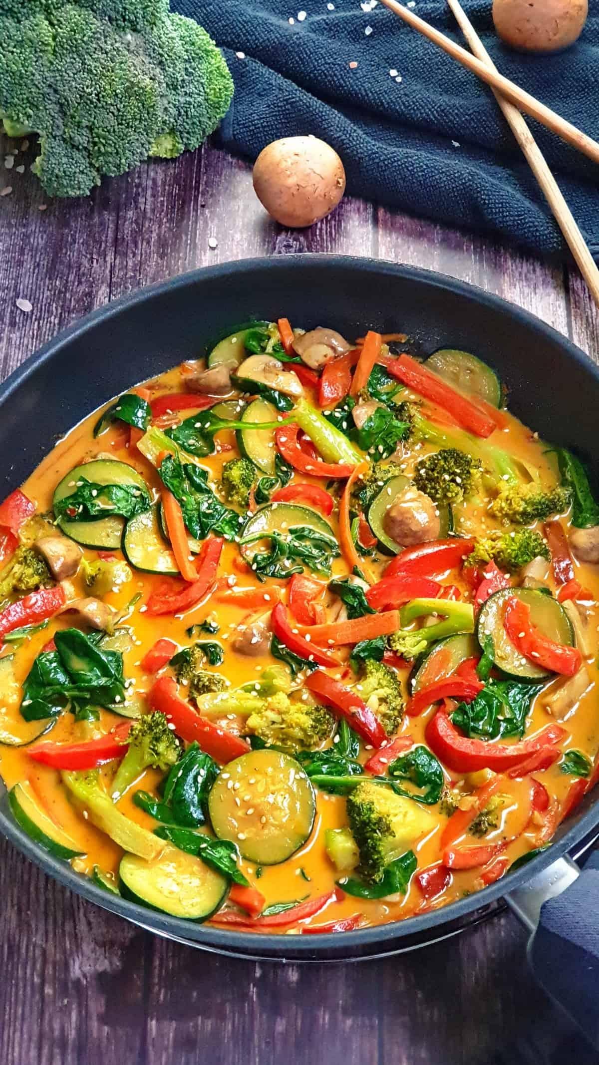 In einer Pfanne ein Gemüse Curry mit Kokosmilch. Mit Sesam bestreut. Im Hintergrund Deko.