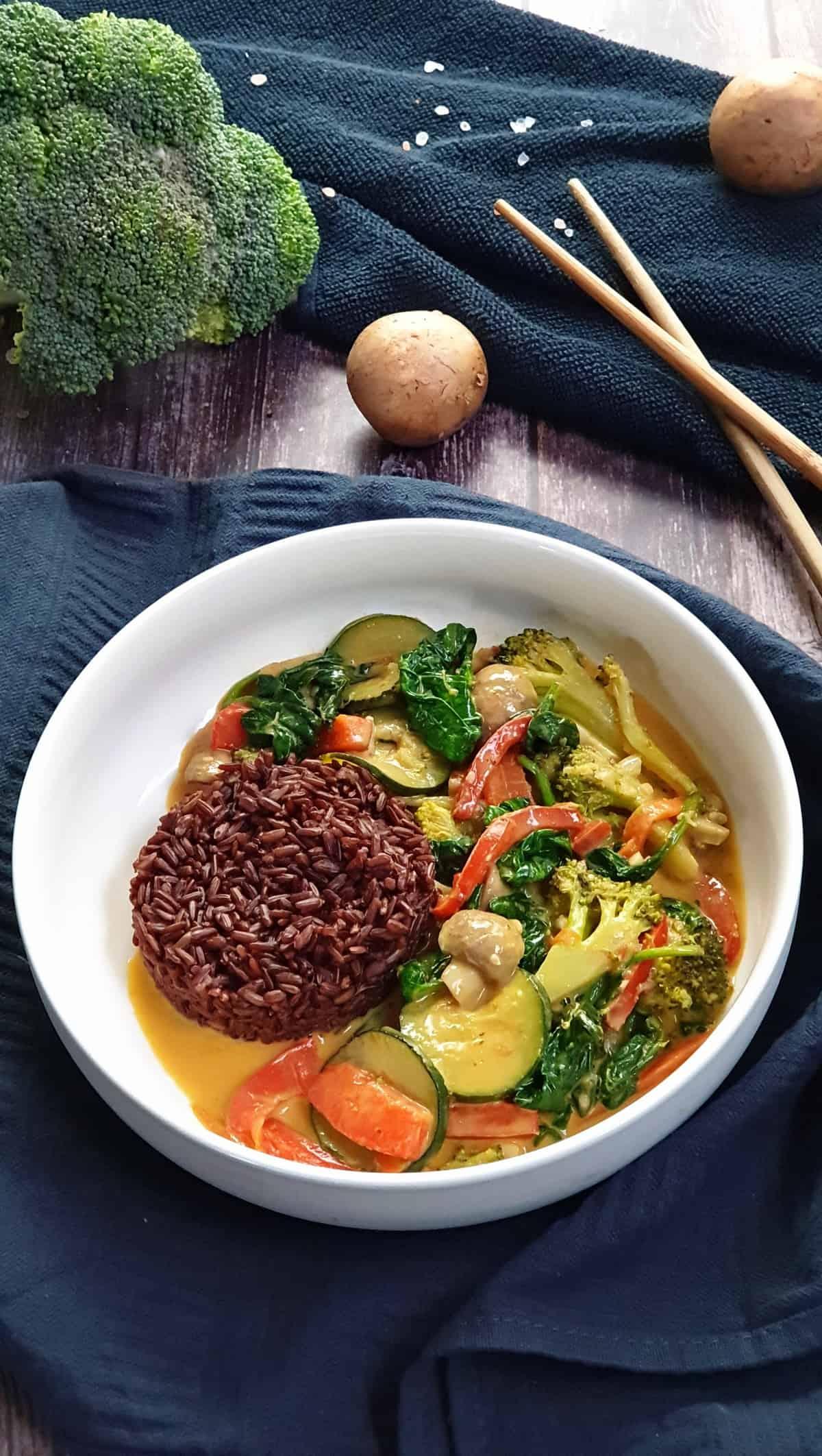 In einer weißen Schale ein Gemüse Curry mit Kokosmilch und Reis. Im Hintergrund Deko.