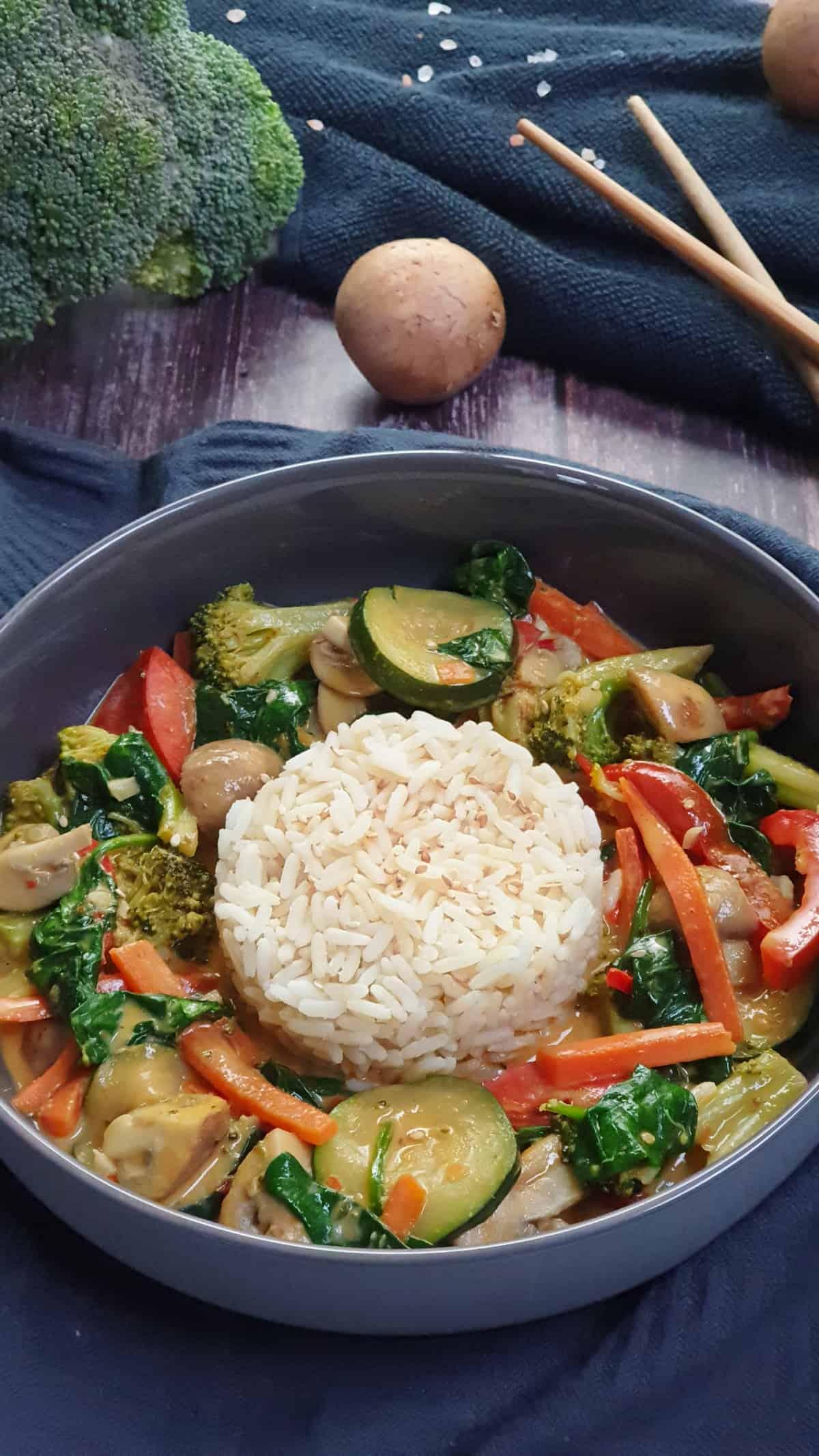 In einer grauen Schale ein Gemüse Curry mit Kokosmilch und Reis. Im Hintergrund Deko.