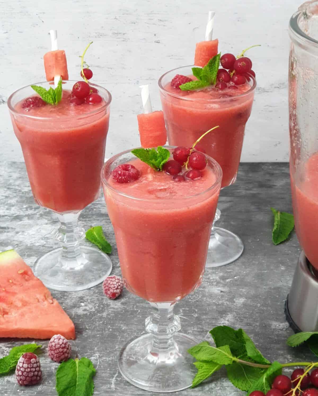 3 Cocktailgläser gefüllt mit Juicy Watermelon Drink. Garniert mit Johannisbeeren, Himbeeren und frischer Minze.