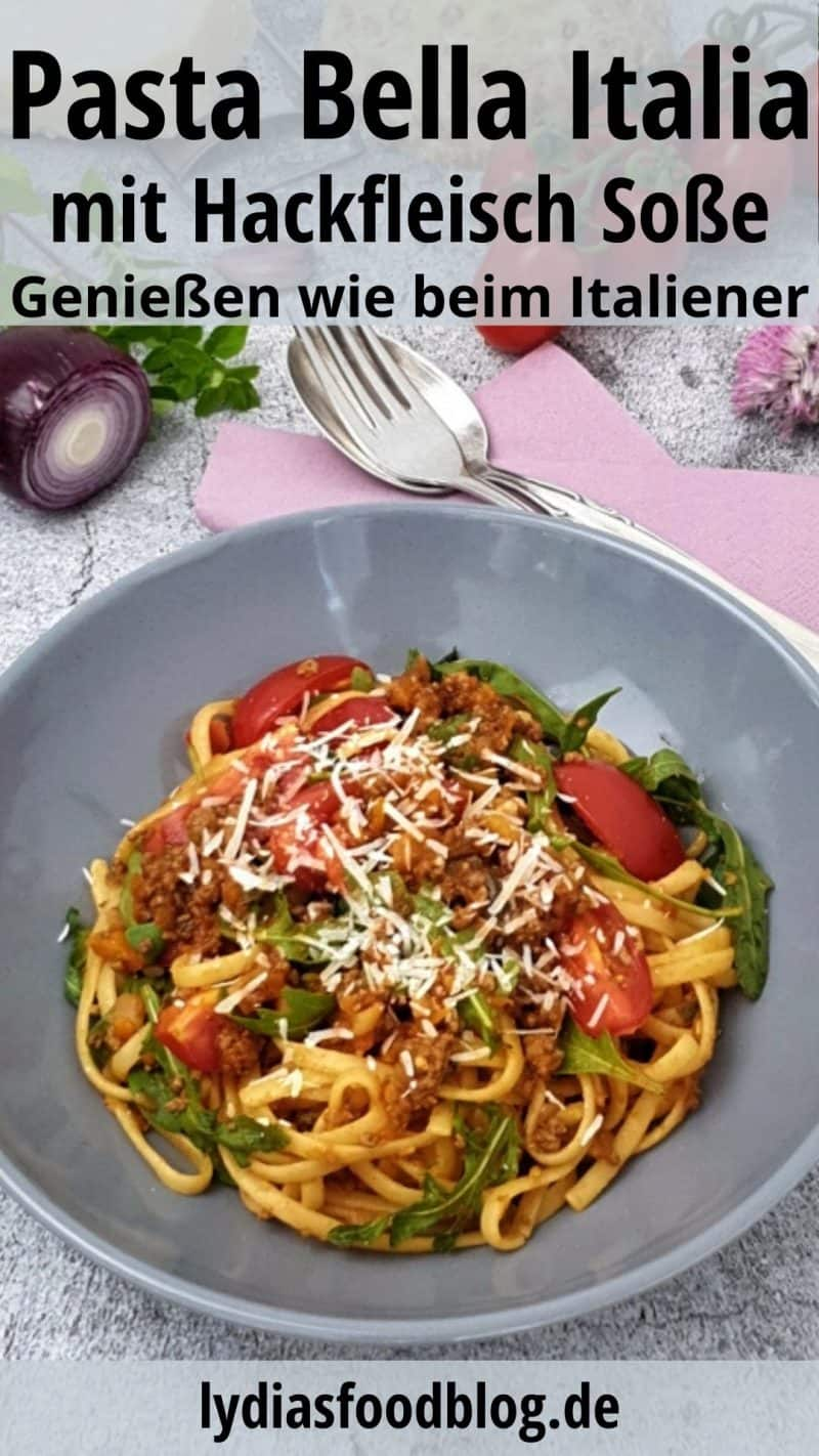 Linguini mit Hackfleisch Soße, Rucola und frischen Tomaten. Angerichtet in einer grauen Schale und mit Parmesan bestreut.