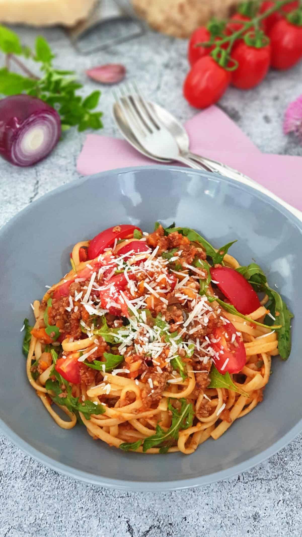 In einer grauen Schale serviert Pasta Bella Italia mit Hackfleisch-Soße und Rucola. Bestreut mit Parmesan. Im Hintergrund Deko.