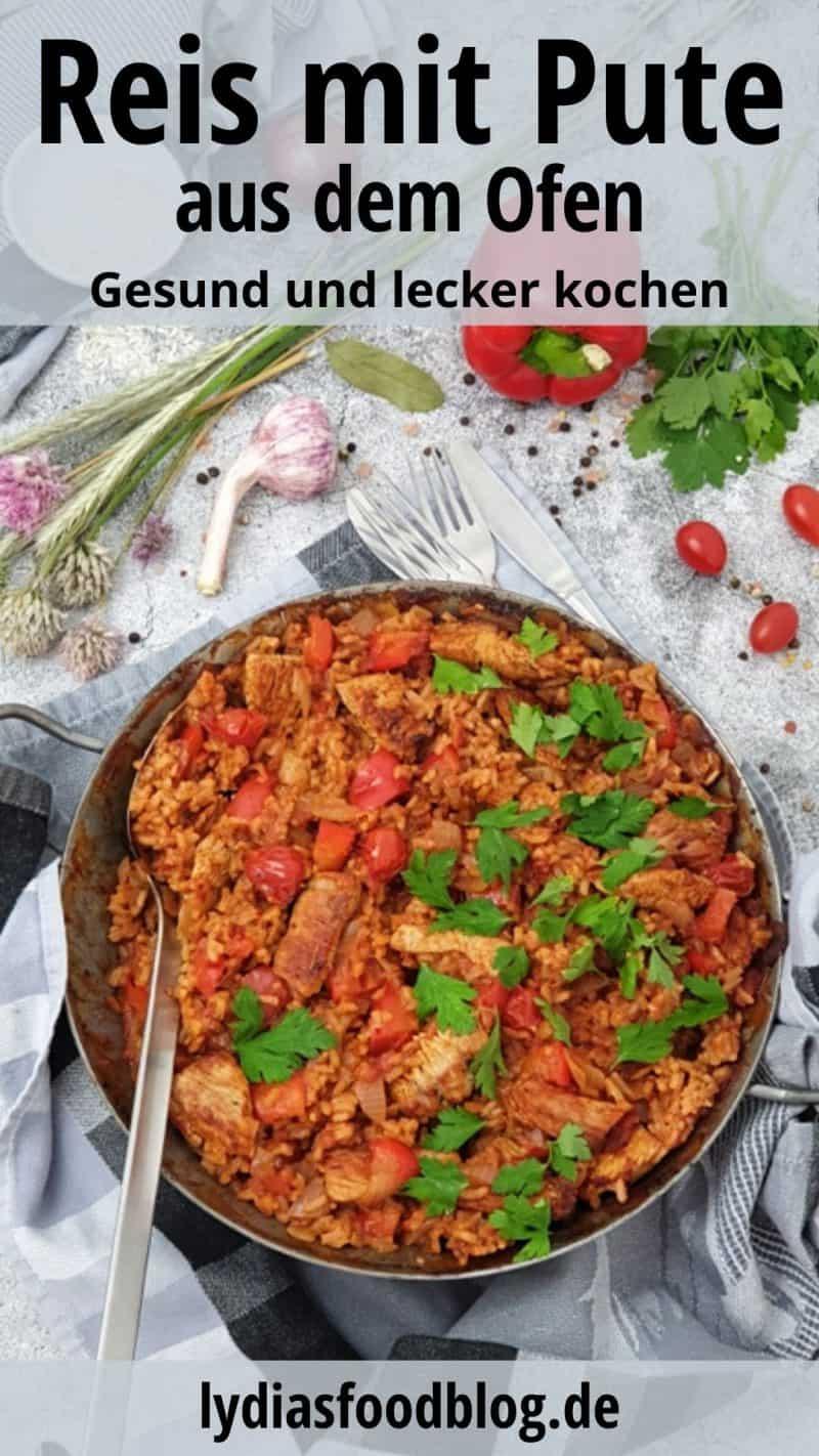In einer gußeisenen Pfanne sieht man ein Ofengericht aus Reis und Pute mit Paprika und Tomate. Bestreut mich frischer Petersilie und dekorativ fotografiert. Im Hintergrund sieht man Paprika, Knoblauch und kleine Tomaten.
