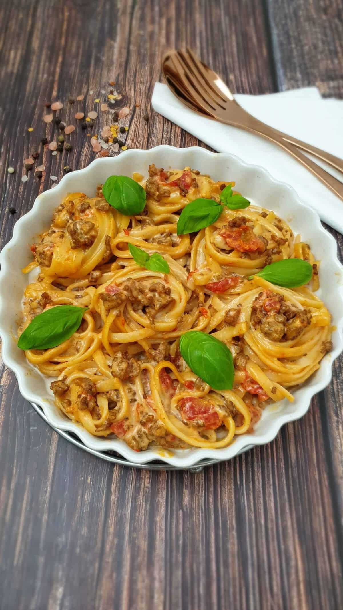 In einer runden weißen Auflaufform Spaghetti Auflauf mit Hackfleisch