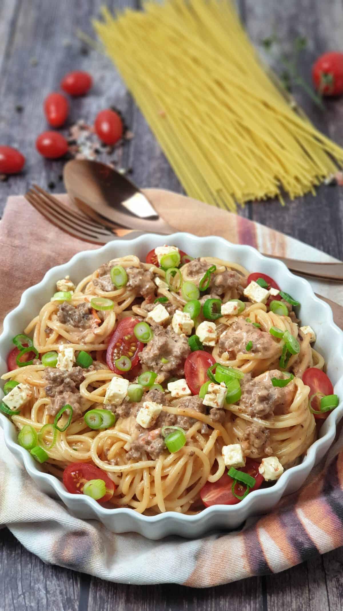 In einer runden weißen Auflaufform Spaghetti Auflauf mit Hackfleisch, Schafskäse und Lauchzwiebeln.