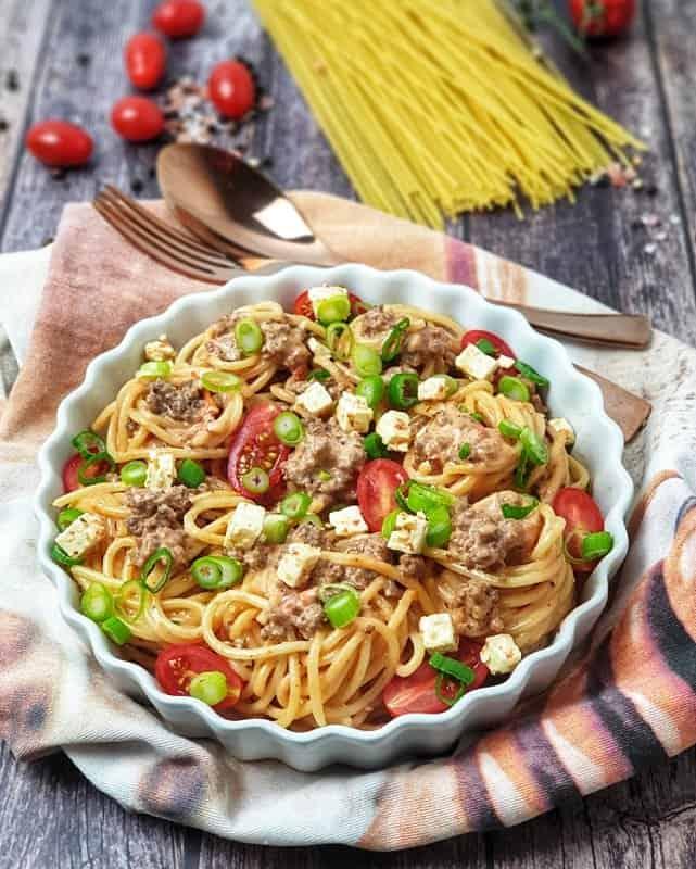 Spaghetti Auflauf mit Tomaten und Hackfleisch in einer cermigen Käsesoße garniert mit Lauch, Feta und Tomaten