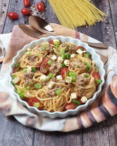 In einer weißen runden Auflaufform sieht man einen Spaghetti Auflauf mit Hackfleisch. Die Nudeln sind zu kleinen Nestern gerollt und mit Feta, Frühlingszwiebeln und kleinen Tomaten garniert.