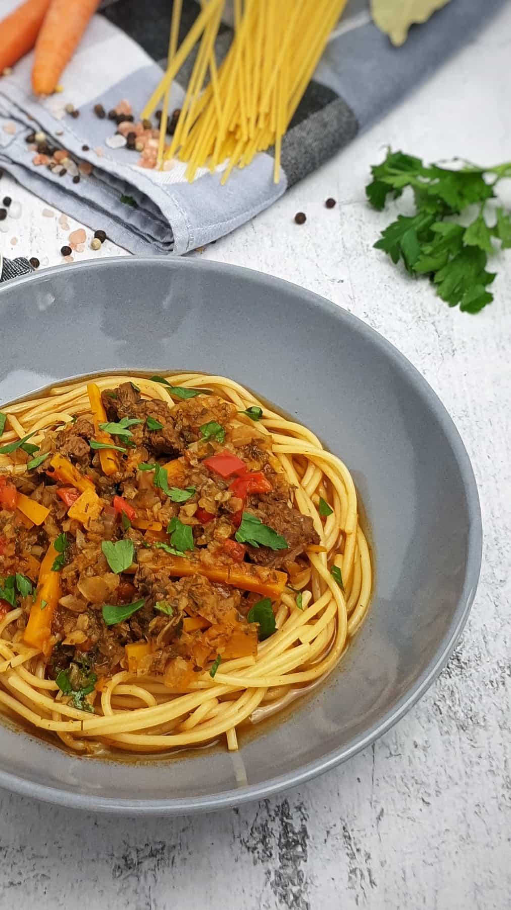 In einer grauen Schale angerichtet Spaghetti mit Lagman-Suppe. Im Hintergrund Deko.