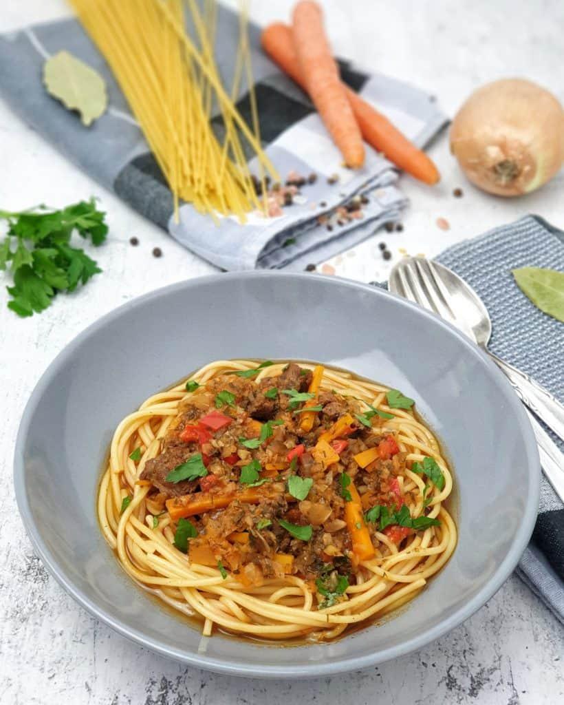 In einer grauen Schale angerichtet Laghman auf Spaghetti. Im Hintergrund Deko.