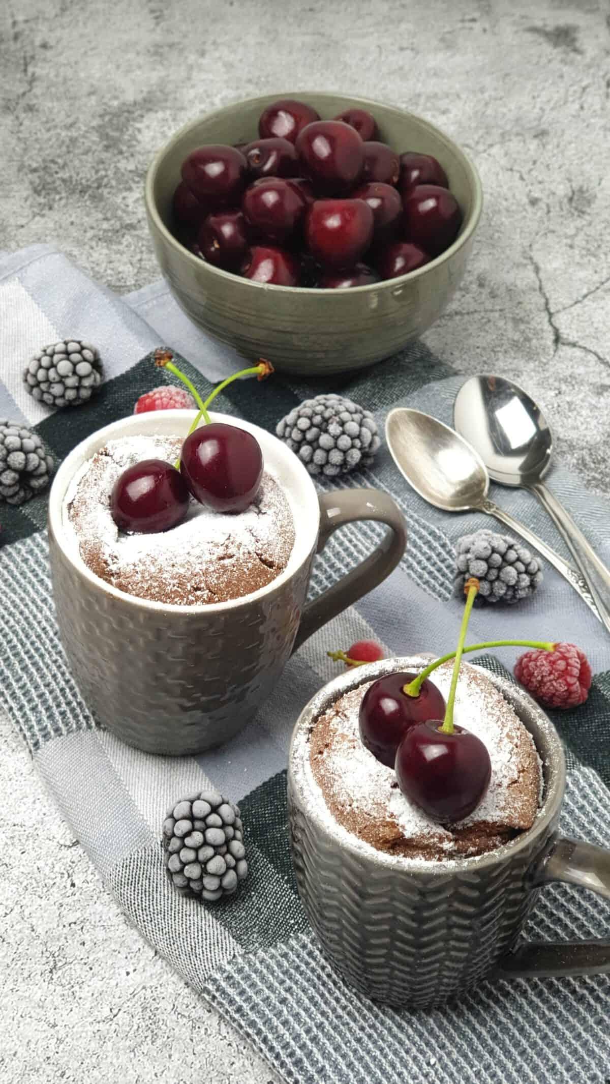 Zwei graue Tassen mit einem Tassenkuchen. Bestreut mit Puderzucker und garniert mit Kirschen.