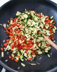 In der Wokpfanne Zucchini Würfel die mit Parikawürfeln angebraten werden.