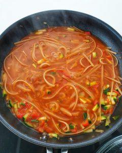 Die Nudeln kochen in der tomatigen Soße mit Gemüse.