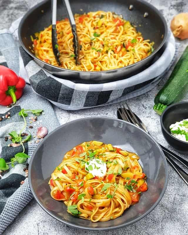 One Pot Pasta mit Paprika und Zucchini in einer grauen Schale angerichtet. Im Hintergrund eine Pfanne in der das Gericht gekocht wurde.