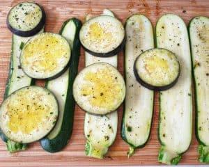 Auf einem Holzbrett in Scheiben geschnittene Zucchini und Aubergine. Das Gemüse ist mit einer Marinade eingestrichen.