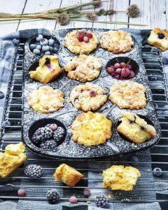 Cheesecake Muffins mit Heidelbeeren und Streuseln in der Muffinform dekorativ angerichtet, mit Zuckerguss und frischen Früchten dekoriert.